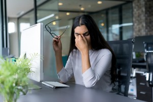 Image of depressed looking businesswoman sitting at computer in office holding glasses and rubbing eyes.